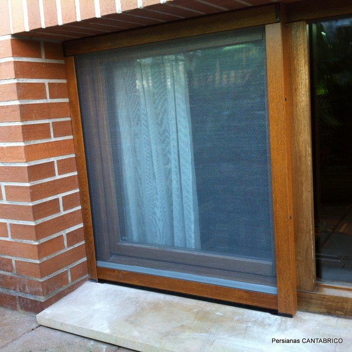 mosquitera enrollable color madera instalada en ventana de madera