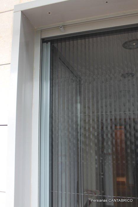 Mosquietra plisada vertical en puerta de acceso a terraza